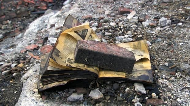 A charred book lies in the rubble near the former municipal library in Lac-Mégantic, Que., Maine libraries are raising funds after 60,000 books, records and photos documenting the Quebec town's history were destroyed in the July explosion following a train derailment.