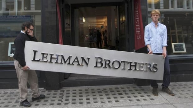 Christie's employees pose for a photograph with a Lehman Brothers sign at Christie's in central London on Sept. 24, 2010.