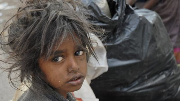 A child sits in front of a garbage dump in Hyderabad, India in 2007. The World Bank estimates that there are still 1.2 billion people living in extreme poverty, defined as living on less than $1.25 per day.