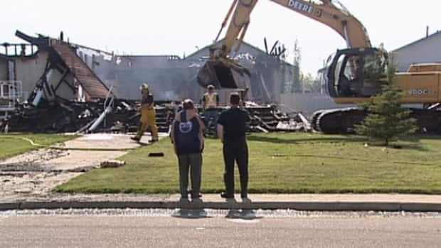 Pastor Bill Wicks and one of the church elders watch as fire crews put out hotspots at the Morinville Baptist Church.