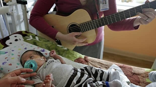 Music therapist Elizabeth Klinger, right, quietly plays guitar and sings for Augustin as he grips the hand of his mother, Lucy Morales, in a newborn intensive care unit in Chicago.