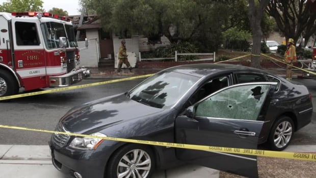 A vehicle sits at the side of a road with a window shattered by bullets that an eyewitness says is connected to a shooting a few blocks away on the campus of Santa Monica College in Santa Monica, Calif. The house in the background was also the scene of a fire said to be connected to the shootings.