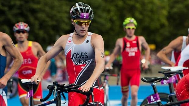 Canada's Kyle Jones runs with his bike in the transition zone as he races in the men's triathlon at the London Olympics on Aug. 7, 2012.
