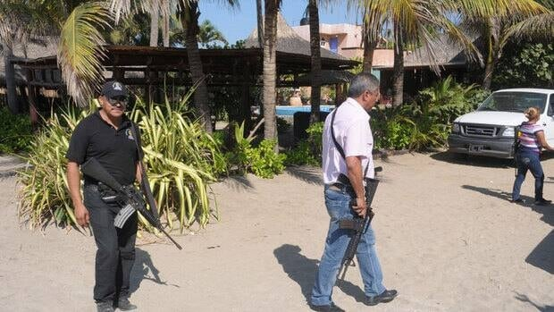 Police in Acapulco patrol outside a beach home where masked armed men broke in and raped six Spanish women.