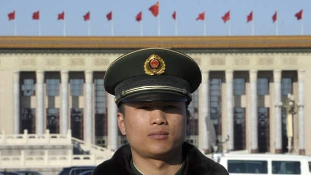 A Chinese paramilitary policeman stands in Tiananmen Square in Beijing on March 14, 2012. China is closing a dozen websites, penalizing two popular social media sites, and has detained six people for circulating rumours of a coup.