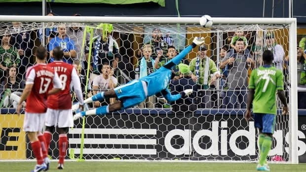 Seattle Sounders player Eddie Johnson, right, watches as Portland Timbers goalkeeper Donovan Ricketts makes a save on a shot by Sounders' Fredy Montero, not shown, in the first half in front of the second largest crowd for an MLS game.