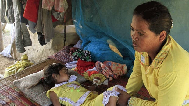 Mean Thida, 4, sleeps beside her mother as she receives treatment for a mystery illness via a bottle of serum. A deadly form of a common childhood illness has been linked to many of the mysterious child deaths in Cambodia in recent weeks.