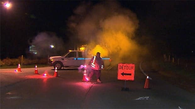 A transportation worker blocks the road near the scene where a 23-year-old Quebec provincial police officer crashed her patrol car Wednesday night.