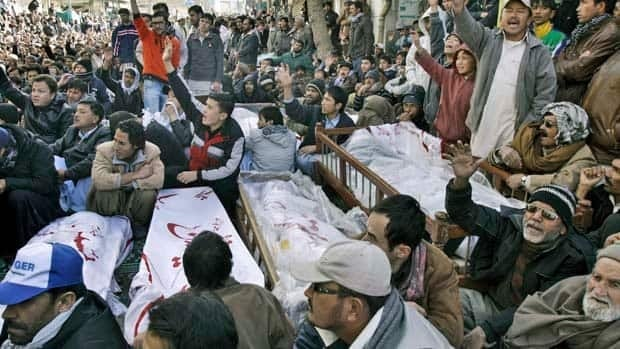 Pakistani Shia Muslims sit next to bodies and await the burial of their relatives and friends who were killed in Thursday's bombings, during a protest Saturday in Quetta.