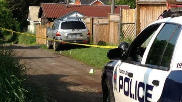 Thunder Bay Police comb through evidence in a laneway behind Lake Street.