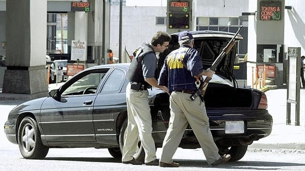 U.S. Customs agents search a car at the Detroit-Windsor Tunnel in downtown Detroit, Tuesday, Sept. 11, 2001. One border expert said the terrorist attacks were a game changer when it comes to border security.