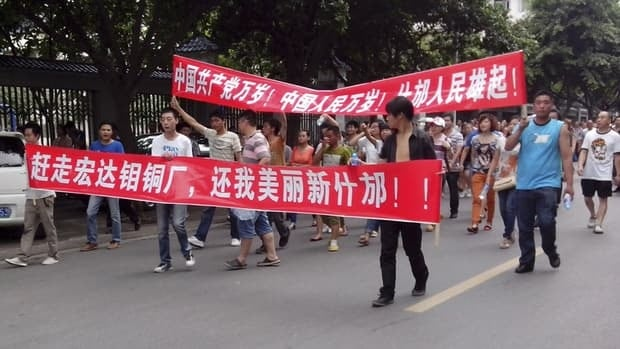 Local residents march with banners during a protest along a street in Shifang, China.