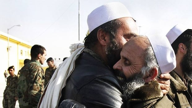 Afghan men hug each other after being released from prison in Kabul, Afghanistan, on Friday. The released prisoners, part of the latest batch of a total of 400 to be released this week, had been captured in operations against the Taliban and other groups.