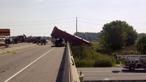 An empty transport truck hangs over a guardrail on Highway 402 near Sarnia. Ontario has pledged $100 million for road and bridge repair in this year's budget.