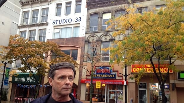 David Blanchard and partners want to tear down the Gore Park storefronts behind him next summer for a grocery store, parking and condo development.