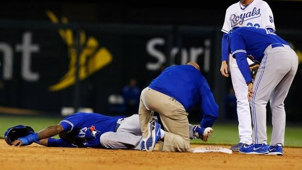 A trainer works on Toronto Blue Jays' Jose Reyes after he injured his leg while stealing second base against the Kansas City Royals.