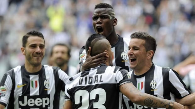 Arturo Vidal of Juventus is mobbed by teammates after scoring the only goal of the match Sunday against Palermo.