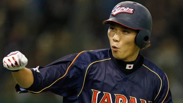 Japan's shortstop Hayato Sakamoto rounds the bases after hitting a grand slam off Netherlands' pitcher Berry Van Driel in the seventh inning in Tokyo on Sunday.