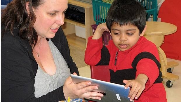 "Teacher Stacie Carroll helps four-year-old Farhan Ahmod, who is austistic and non-verbal, use an iPad at the Beverley School in 2011. Teachers and students at the school were involved in a research project with the University of Toronto to see if ""touch technology"" improves the communication, social interaction and academics of students with developmental disabilities such as autism."