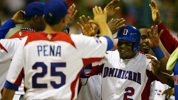 Erick Aybar (2) of the Dominican Republic celebrates scoring a run against Venezuela during the first round of the World Baseball Classic action on Thursday. (Photo by Al Bello/Getty Images)