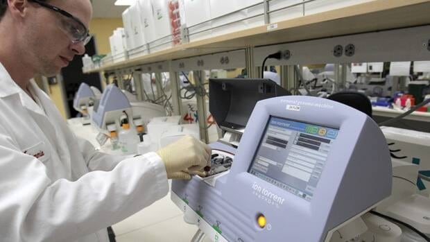 A scientist works with a machine that reads DNA at the Life Technologies laboratory in Carlsbad, Calif. The company says its machine can decode a human genome in a day for $1,000 US.