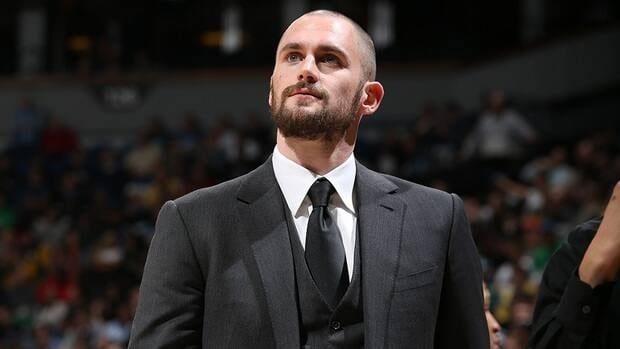Kevin Love of the Minnesota Timberwolves looks on from the bench against the Sacramento Kings during his team's season opening game. Love was expected to be sidelined for close to two months, but makes his debut after just four weeks.