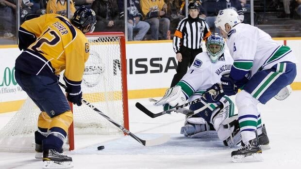 Nashville Predators centre Mike Fisher (12) scores against Vancouver Canucks goalie Roberto Luongo (1) and Canucks' Sami Salo (6) in the second period on Tuesday in Nashville, Tenn.
