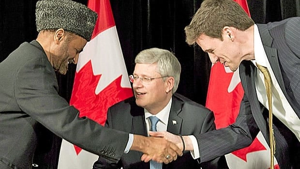 Muslim cleric Lai Khan Malik greets Canada's new ambassador for religious freedom, Andrew Bennett, in February, as the prime minister looks on.