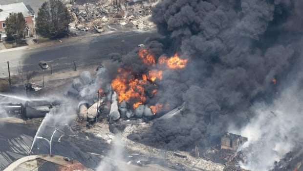 A July 6, 2013, file photo shows smoke rising from railway cars that were carrying crude oil after derailing in downtown Lac-Mégantic, Que. The U.S. Federal Rail Administration has announced new safety rules to prevent a similar disaster, which killed 47 people.
