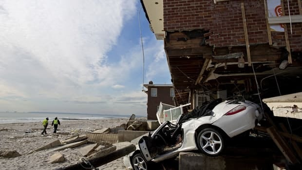 A badly damaged home is entangled with a vehicle along the beach in the Belle Harbor section of the Rockaway neighborhood in the wake of Hurricane Sandy.