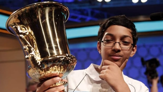 "Arvind Mahankali of New York holds his trophy after winning the Scripps National Spelling Bee  by correctly spelling ""knaidel,"" a kind of dumpling."