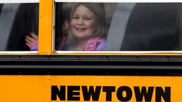 A young girl waves as her school bus pulls into Hawley School on Dec. 18, in Newtown, Conn. Classes resumed Tuesday for Newtown schools except those at Sandy Hook. Buses ferrying students to schools were festooned with large green and white ribbons on the front grills, the colours of Sandy Hook. At Newtown High School, students in sweatshirts and jackets, many wearing headphones, betrayed mixed emotions. Adam Lanza walked into Sandy Hook Elementary School in Newtown on Dec. 14 and opened fire, killing 26 people, including 20 children, before killing himself.