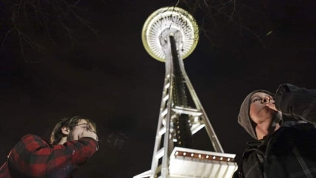 People light up near the Space Needle after the law legalizing the recreational use of marijuana went into effect in Seattle on Thursday.