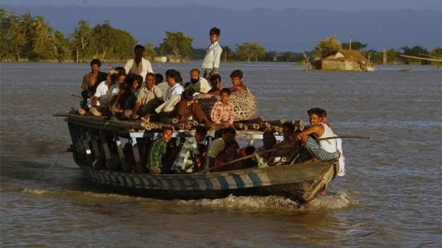 Flood affected villagers crowd a boat in Gagalmari village in Assam state, India. The floods from monsoon rains in northeastern India killed dozens of people, with more than 2,000 villages inundated as rivers breached their banks, an official said Sunday.