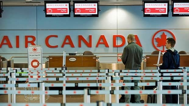 Passengers queue at an Air Canada check-in desk at Trudeau Airport in Montreal.
