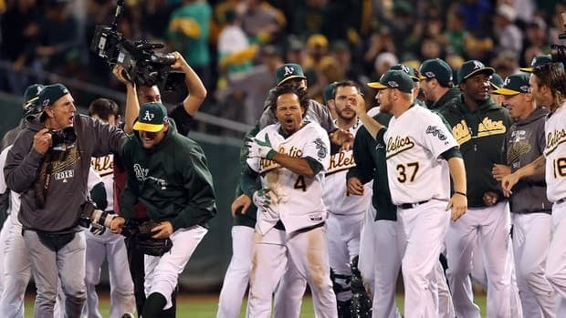 Coco Crisp of the Oakland Athletics is congratulated by teammates after he hit a game-winning single to beat the Detroit Tigers in the ninth inning of Game 4 on Wednesday.