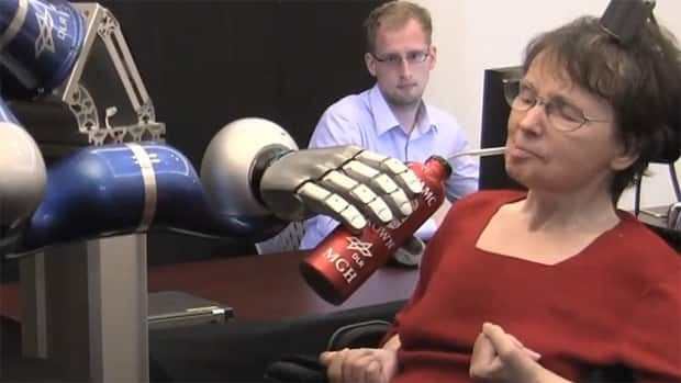 Cathy Hutchinson of East Taunton, Mass., controls a robotic arm with her mind to feed herself coffee.