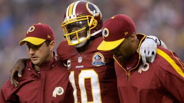 Washington Redskins quarterback Robert Griffin III is helped off the filed after an injury during the second half against the Baltimore Ravens on Sunday.