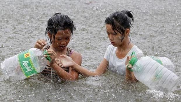 Residents wade on a flooded street during a heavy downpour in the Philippines, where Typhoon Saola has killed 14 people.