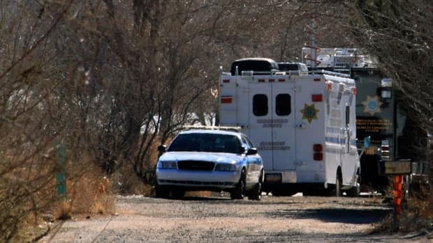 Bernalillo County authorities stationed Sunday outside a home south of Albuquerque, N.M., where two adults and three children were found shot to death. Authorities say a teenager has been arrested and booked on murder and other charges in connection with the shootings.