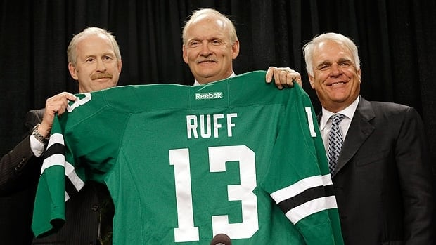 Lindy Ruff, centre, poses with the new Dallas Stars jersey, flanked by general manager Jim Nill, left, and team president Jim Lites.
