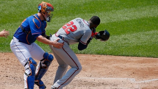 Jason Heyward of the Atlanta Braves is helped after getting hit in the face with a pitch from Jonathon Niese in the fifth inning at Citi Field on August 21, 2013 at Citi Field in New York City.