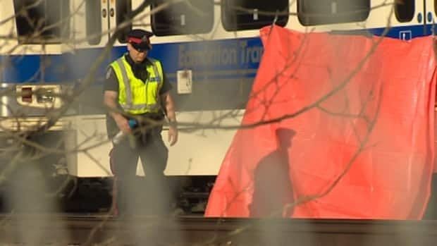 A police officer walks near where a man's body was found on the LRT tracks on Monday morning. Police have since ruled the man's death non-criminal.