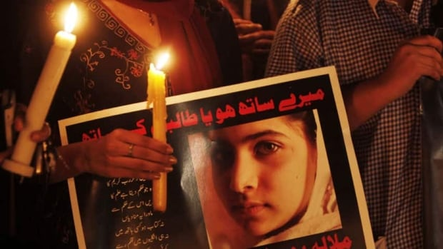 A Pakistani protester holds a candle and a poster during an Oct. 11 vigil in Islamabad that reads, 'Are you with us or the Taliban? Long live Malala Yousafzai.'