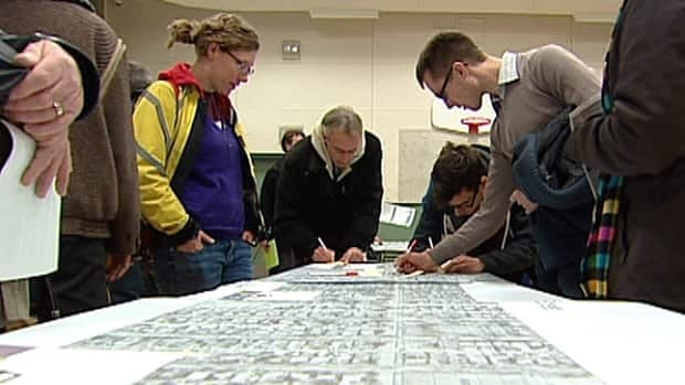 Area residents examine a map of the proposed bike lanes in south Edmonton Tuesday night at Hazeldean School.