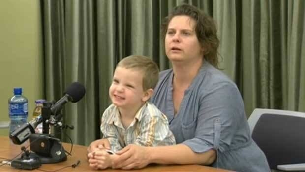 Three-year-old Luke Turner smiles as his mother, Brandy Turner, fields questions from reporters after the pair landed in Denver late Tuesday evening.