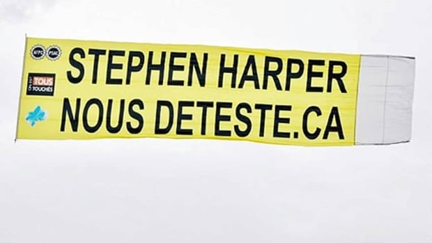 "An airplane towing this aerial banner, which translates as ""Stephen Harper hates us"" in English, was ordered grounded by the RCMP on Saturday."