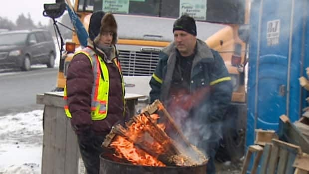 Two striking maintenance workers try to stay warm on a picket line at the St. John's International Airport earlier this year.