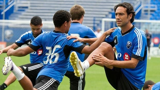 Former Milan defender Alessandro Nesta, right, stretches with teammate Evan James during his first practice after signing with the Montreal Impact.