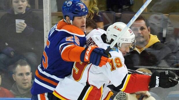 Andy Sutton makes contact for Edmonton on Calgary's Blair Jones during a 2011-12 game, with the Oilers his last stop in the NHL.
